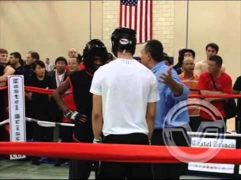 Judge Gus Kaparos officiating a match between two fighters at The US Open Martial Arts Championship